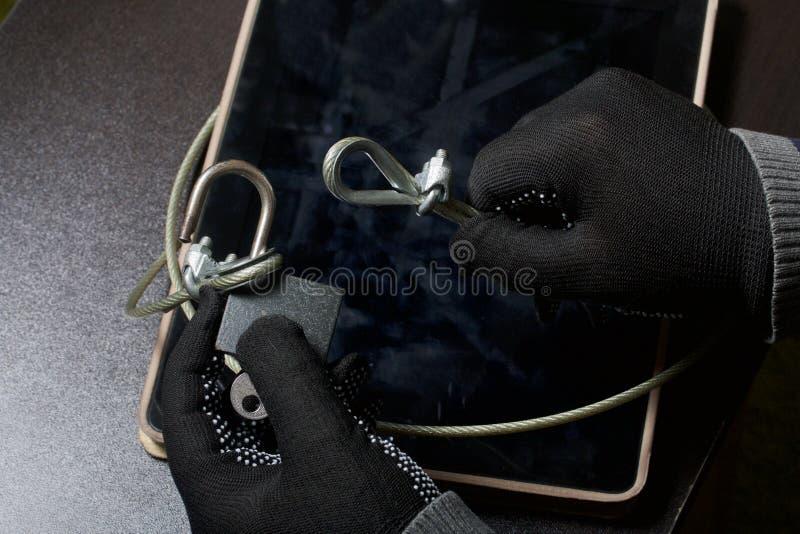 Seguridad de ordenador Protección del acceso a los datos La tableta es protegida por un cable de la seguridad y una cerradura Un  fotografía de archivo libre de regalías