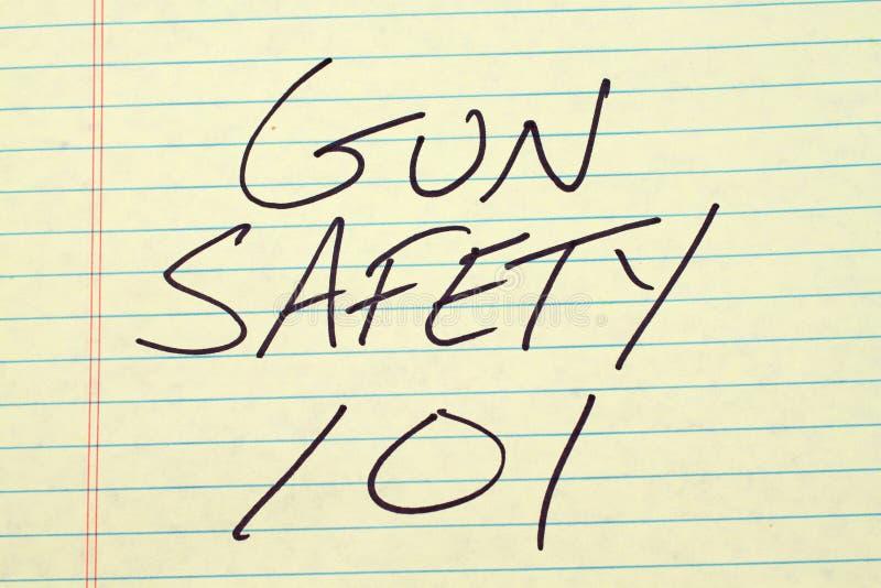 Seguridad 101 del arma en un cojín legal amarillo imagen de archivo