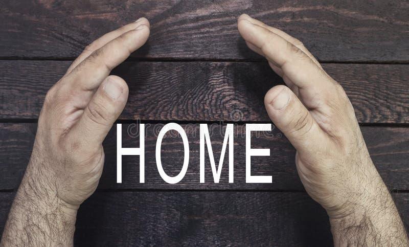 Seguridad del concepto de la propiedad, seguro casero El ` s del agente de seguro da a protectubg el texto casero en la madera foto de archivo