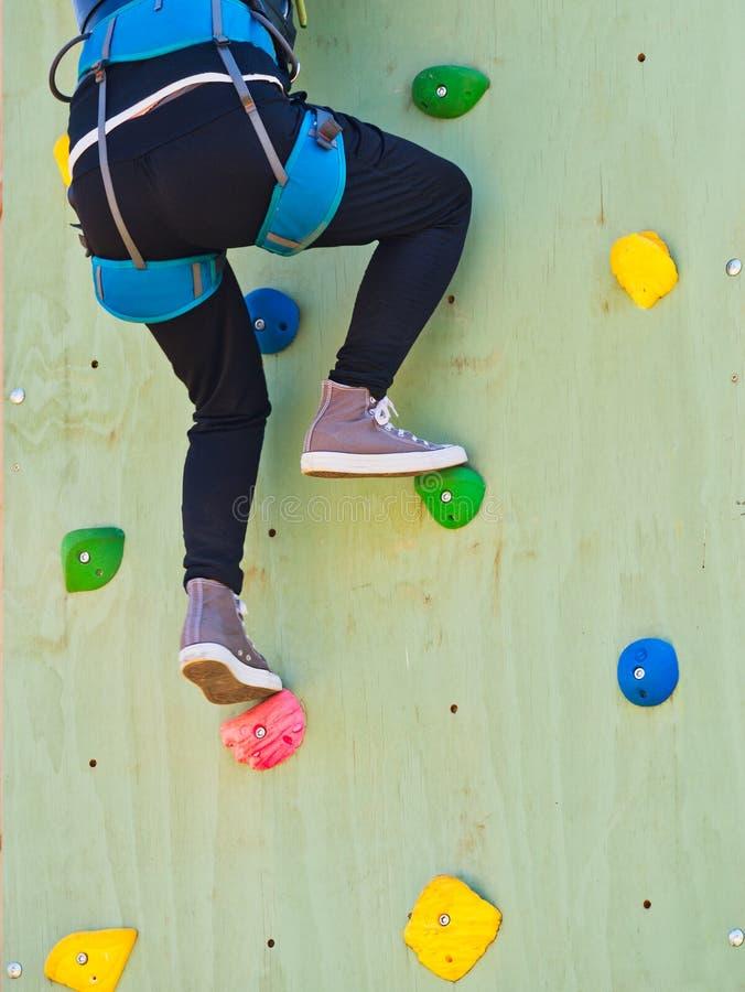 Seguridad del deporte de la pared de la mujer joven de la vista posterior del primer que sube Desafíe el concepto imagen de archivo