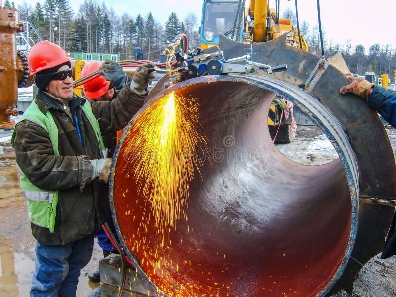 Seguridad en el trabajo Soldadura e instalación de la tubería Soldadores y ajustadores industriales de los días laborables foto de archivo