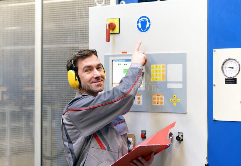 Seguridad en el trabajo: trabajadores en una planta industrial con el prote del oído fotos de archivo libres de regalías