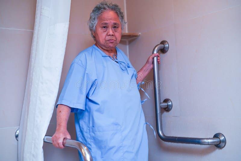 Seguridad paciente asi?tica de la manija del cuarto de ba?o del retrete del uso de la mujer mayor o mayor de la se?ora mayor en s fotos de archivo