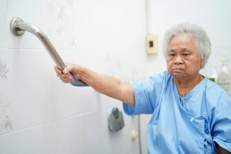 Seguridad paciente asi?tica de la manija del cuarto de ba?o del retrete del uso de la mujer mayor o mayor de la se?ora mayor en s imagen de archivo