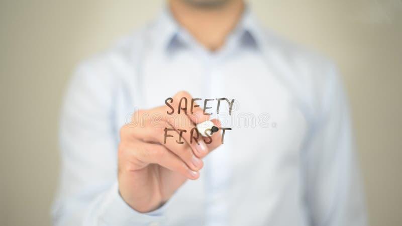 Seguridad primero, escritura del hombre en la pantalla transparente imagen de archivo