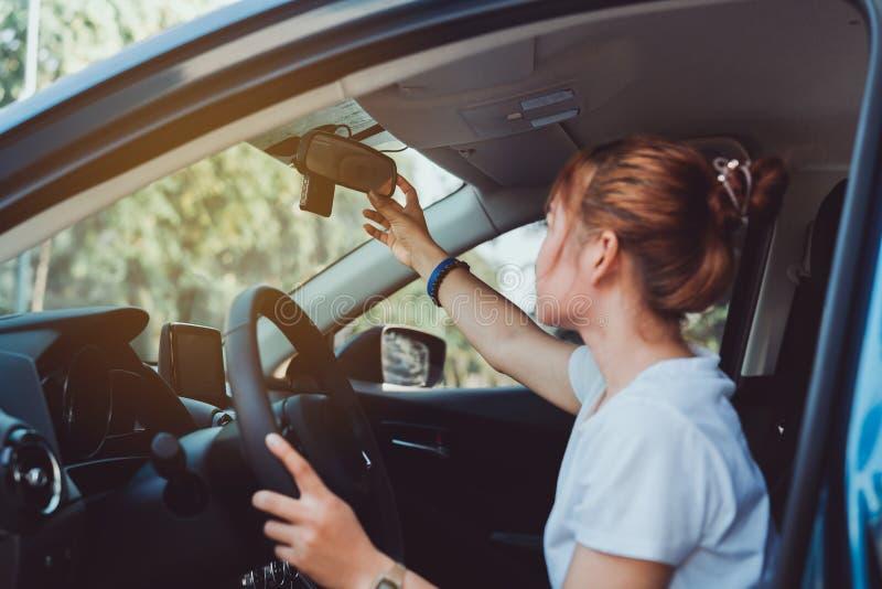 Seguridad que conduce a la mujer para ajustar el espejo retrovisor del coche imágenes de archivo libres de regalías