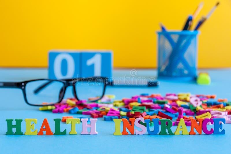 Seguro médico - palabra integrada por pequeñas letras coloreadas en el lugar de trabajo del negocio del doctor, o agente de segur fotografía de archivo libre de regalías