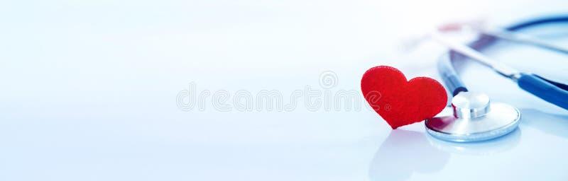Seguro médico y concepto médico de la enfermedad cardíaca de la atención sanitaria, una forma roja del corazón con el estetoscopi imagen de archivo libre de regalías