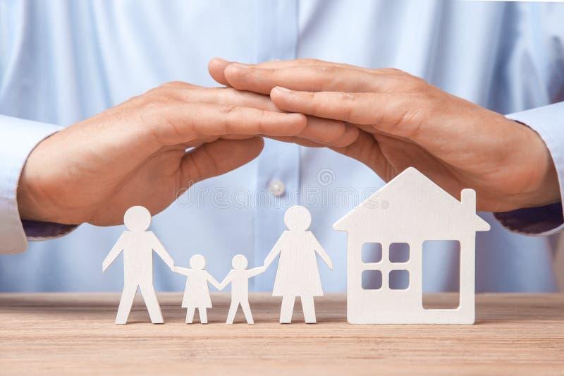 Seguro y hogar de la familia El hombre en camisa cubre a su familia con su padre, madre, hijo e hija y la casa imagen de archivo