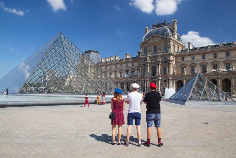 Sehen Sie auf Louvrepyramide in Paris und drei jungen Leuten mit Brustbeeren an lizenzfreie stockfotos