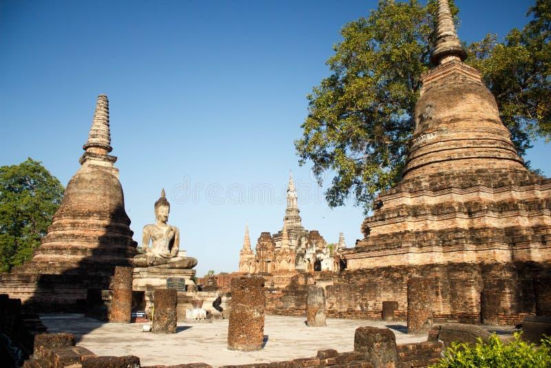 Sehen Sie zu den Ruinen und sitzenden zur Buddha-Statue an Wat Mahathat-Tempel in historischem Park Sukhothai an stockfotos