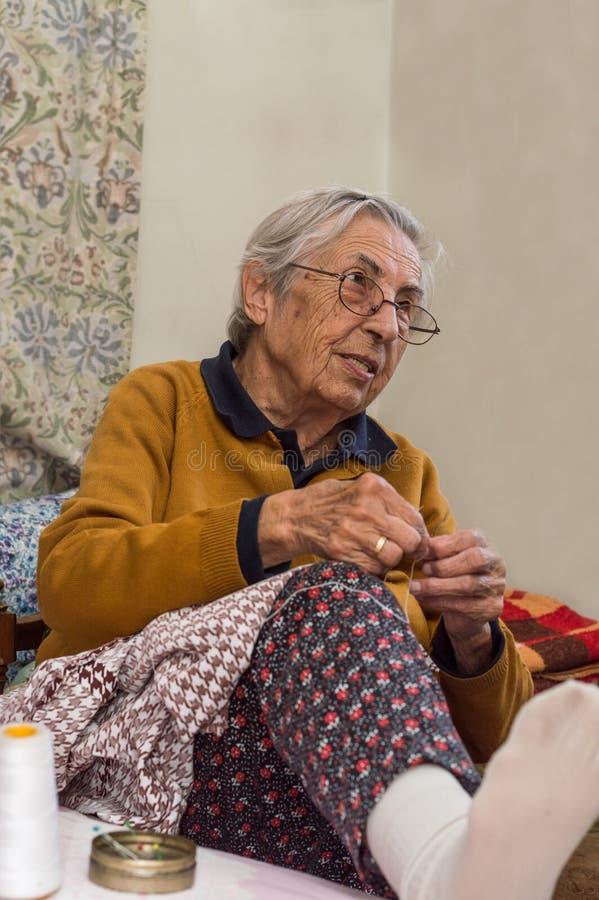 Sehr alte ältere Frau, die in ihrem Raum näht lizenzfreie stockbilder