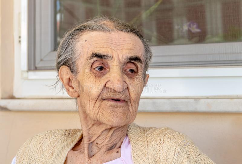 Sehr alte ältere Frau, die im Balkon an einem Sommertag sitzt lizenzfreies stockbild