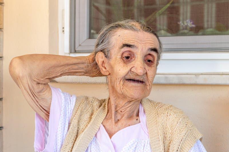 Sehr alte ältere Frau, die im Balkon an einem Sommertag sitzt lizenzfreie stockbilder