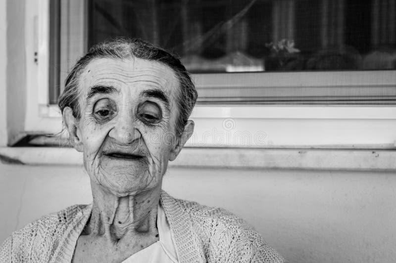 Sehr alte ältere Frau, die im Balkon an einem Sommertag sitzt lizenzfreie stockfotografie