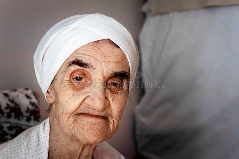 Sehr alte ältere Frau mit der Mütze, die in ihrem Raum sitzt lizenzfreie stockfotografie