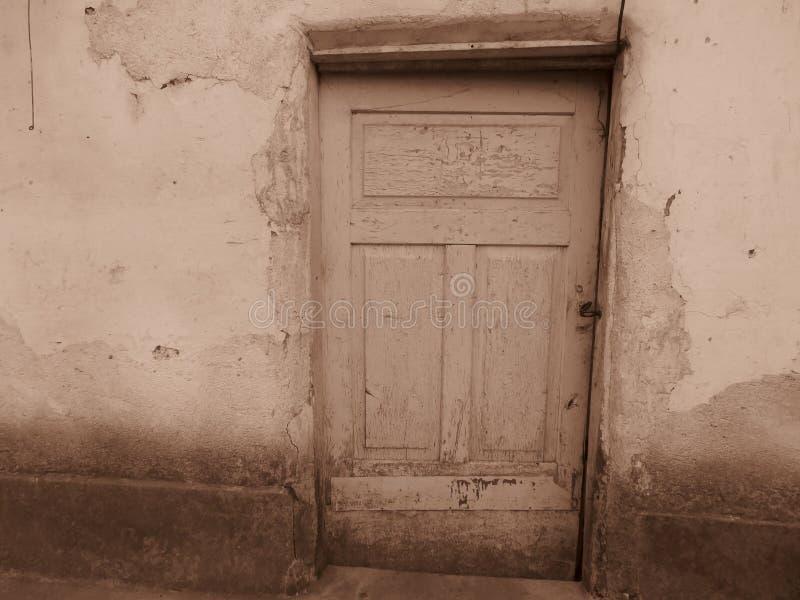 Sehr alte isoleted defekte Holzhaustür in der Sepiafarbe lizenzfreies stockbild