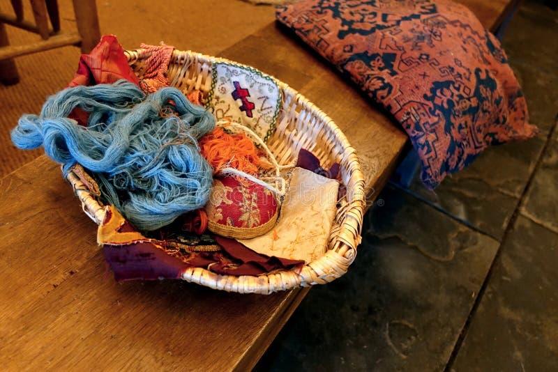 Sehr alter antiker Nähen oder Kurzwarenkorb mit Wolle, Garn, Thread und verschiedenen Stücken Leinen und anderen Geweben, auf ein stockfotos