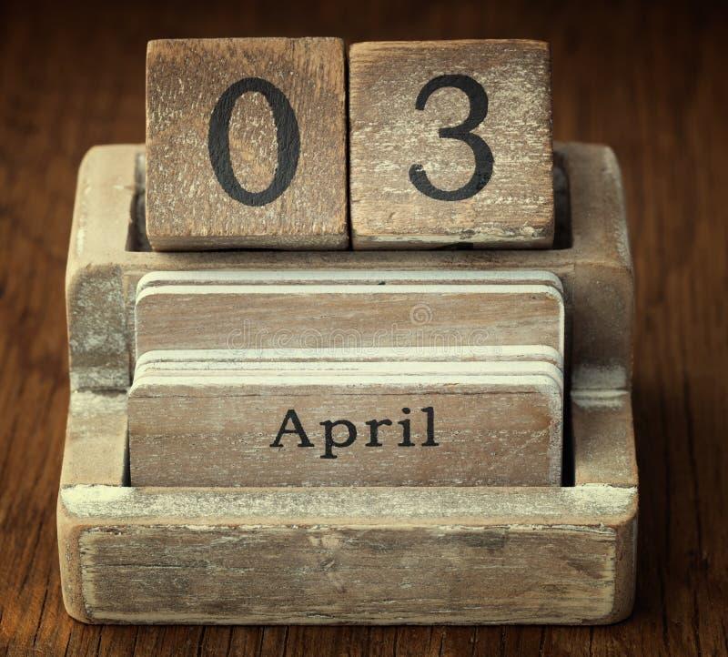 Sehr alter hölzerner Weinlesekalender, der an das Datum am 3. April zeigt lizenzfreie stockbilder