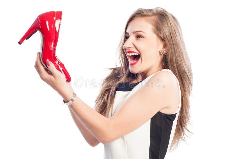 Sehr aufgeregte Frau, die Rotschuhe des hohen Absatzes hält lizenzfreies stockbild