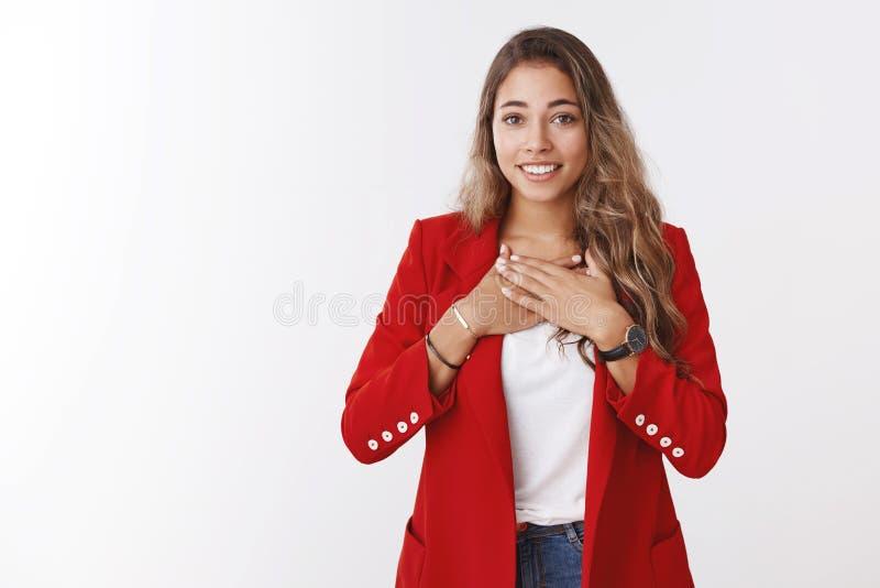 Sehr dankbare junge nette freundlich-aussehende hübsche Frau, die dankbares lächeln der Palmenbrust breit dankender Retter hält lizenzfreie stockfotografie