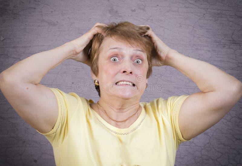 Sehr emotionale Frau auf einem grauen Hintergrund stockbild
