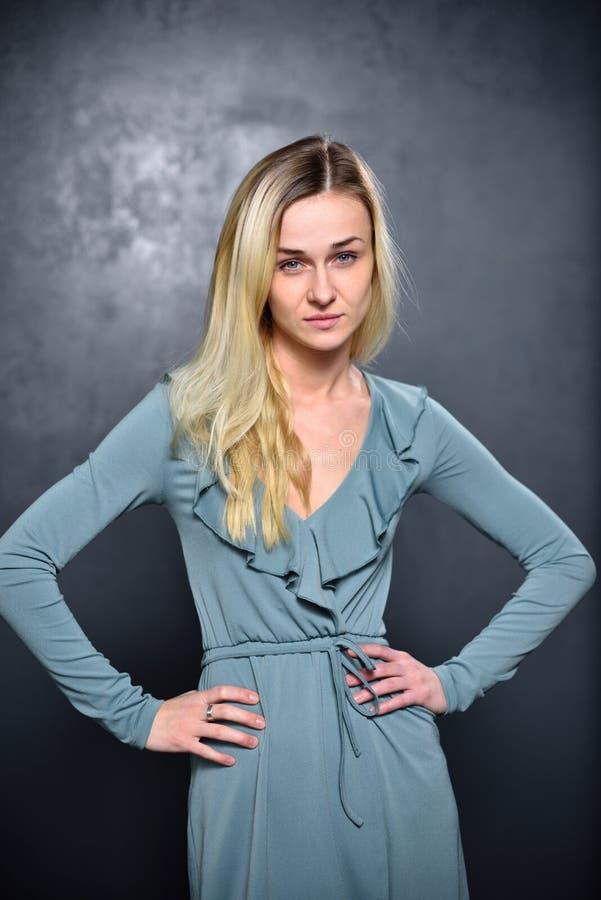 Sehr ernstes blondes Mädchen auf einem grauen Wandhintergrund lizenzfreies stockfoto