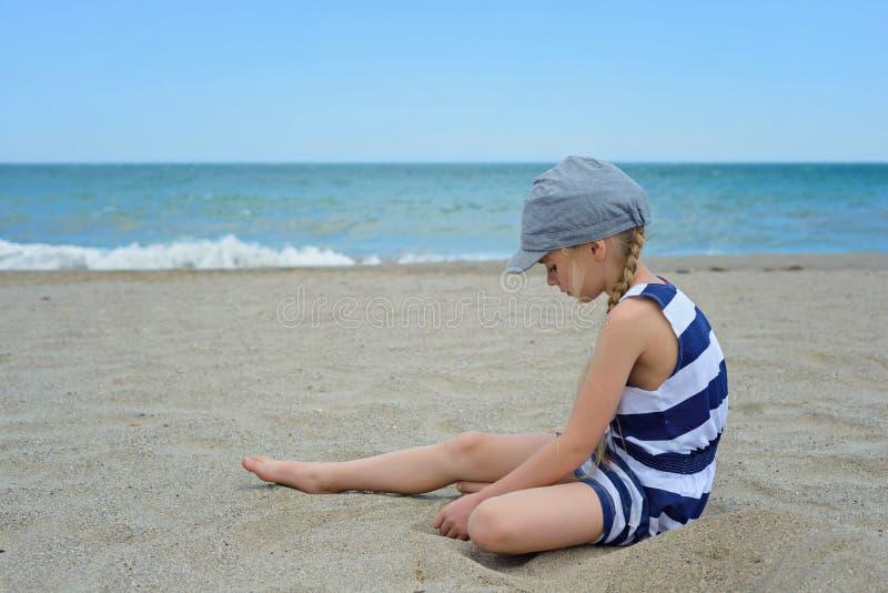 Sehr ernstes nettes kleines Mädchen, das auf dem Strand sitzt lizenzfreie stockfotografie