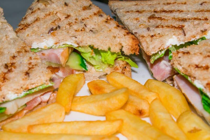 Sehr geschmackvolle Hühnerclub Sandwiche auf einer Platte sind- auf einer weißen Hintergrundnahaufnahme stockfotografie