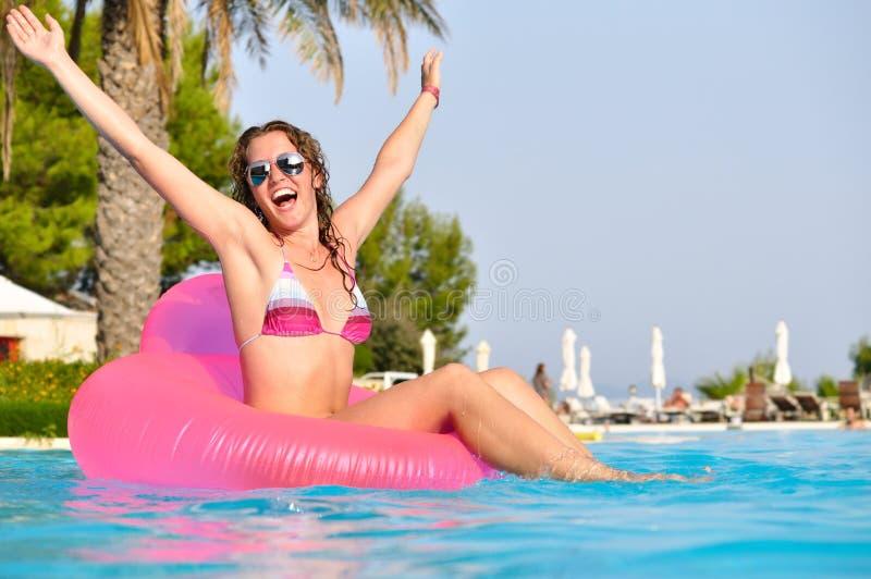 Sehr glückliche Frau auf rosafarbenem Luftbett stockfoto