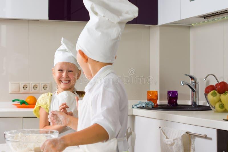 Sehr glückliche kleine Chefs, die in der Küche backen lizenzfreies stockbild