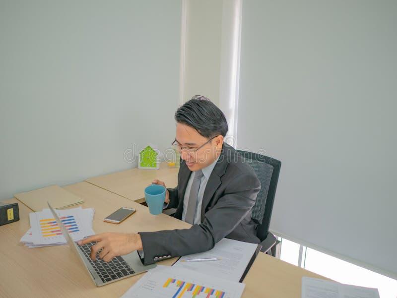 Sehr glücklicher asiatischer Geschäftsmann im Büro lizenzfreies stockbild