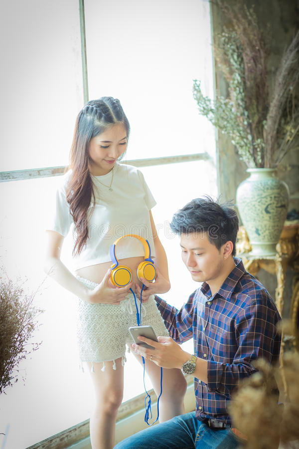 Sehr glücklicher schöner junger Mann und Frau schwangerer Bauch hören t lizenzfreie stockfotos