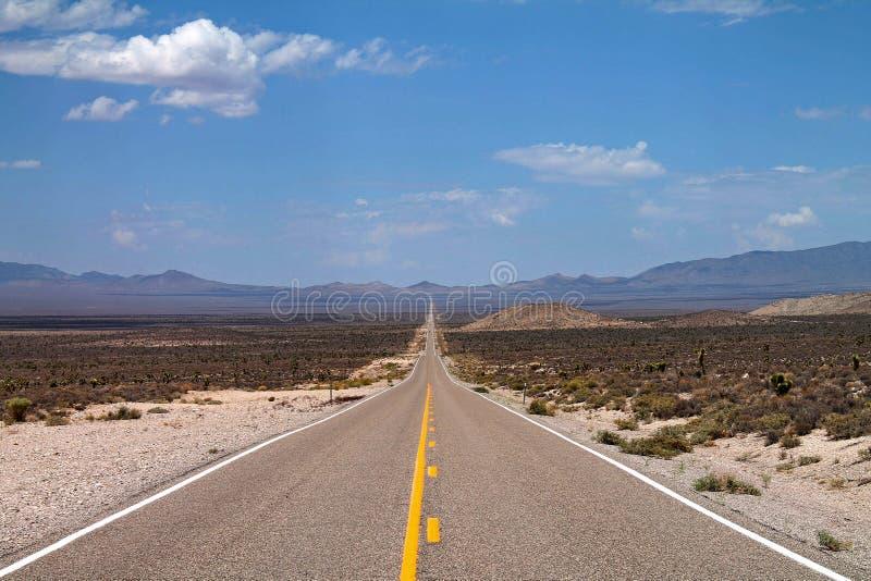 Sehr lang, leere Straße, die durch die Wüste in Nevada ausdehnt stockbilder
