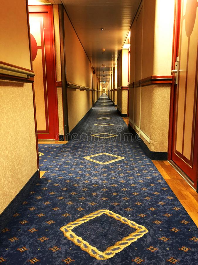 Sehr langer Korridor des Ozean-Kreuzschiffs Räume an beiden Seiten Langer Korridor mit geschlossenen Kabinen des Kreuzschiffs stockfotos