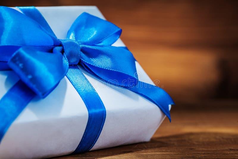 Sehr nah herauf weißes giftbox mit blauem Band auf Weinleseholz stockbilder