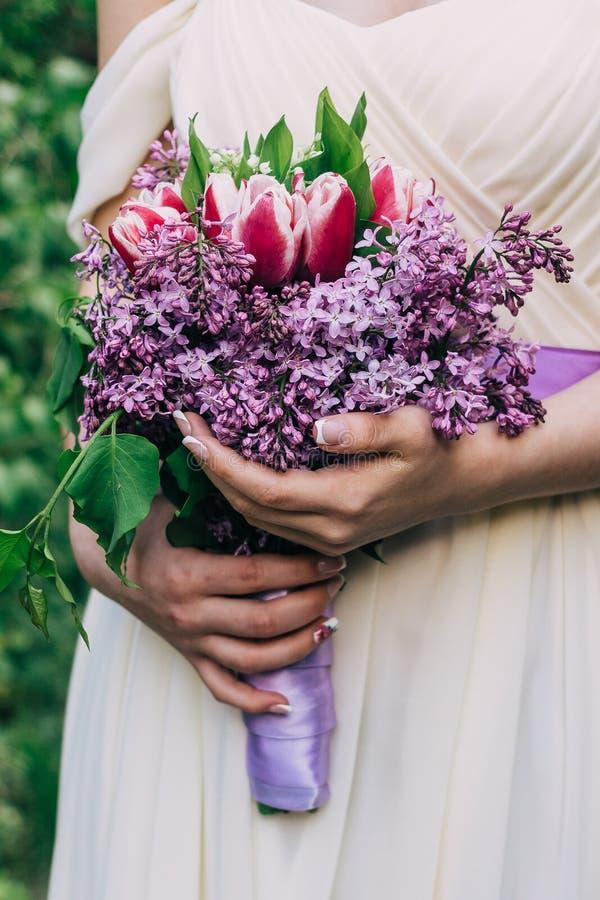 Sehr nette junge Frau, die großen und schönen bunten Blumenhochzeitsblumenstrauß hält stockfotografie