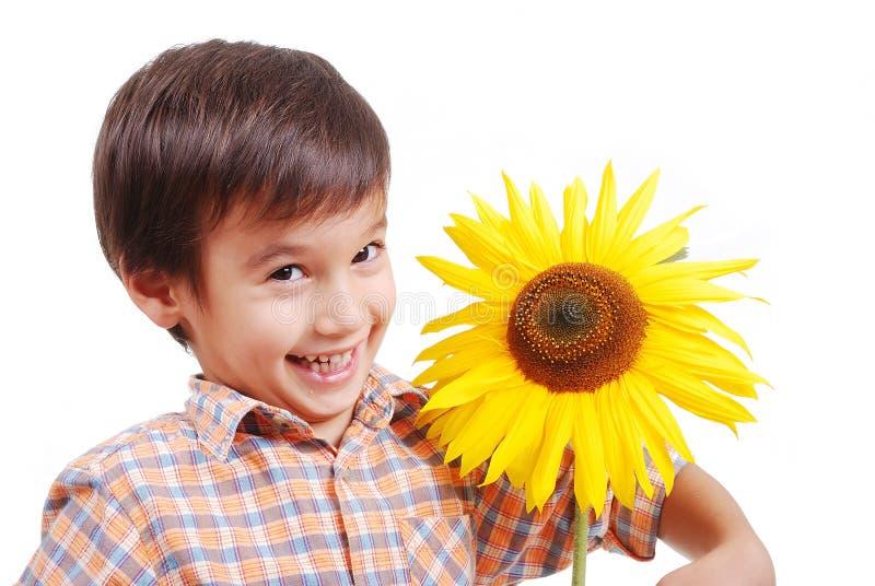 Sehr netter Junge, der Sonnenblume als Freund umarmt lizenzfreie stockfotografie