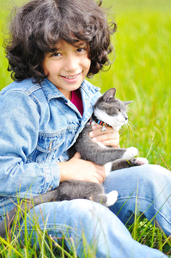 Sehr nettes kleines Mädchen mit Katze auf Wiese lizenzfreie stockbilder