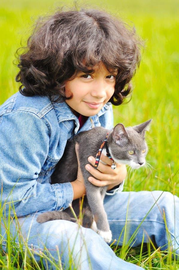 Sehr nettes kleines Mädchen mit Katze auf Wiese lizenzfreie stockfotos