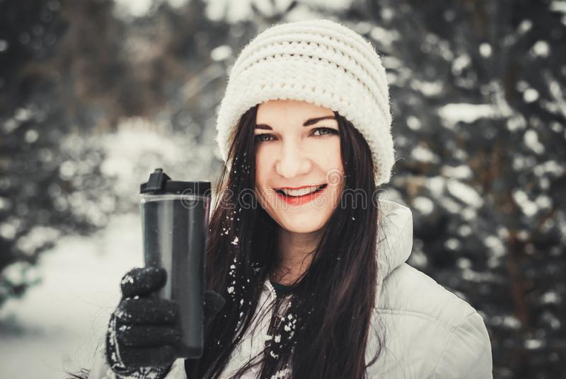 Sehr positive Frau trinkt Kaffee im Winterpark Winterportrait der jungen Frau lizenzfreie stockbilder