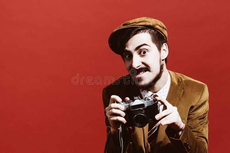 Sehr positiver Fotograf, der im Studio mit Filmkamera aufwirft stockfoto