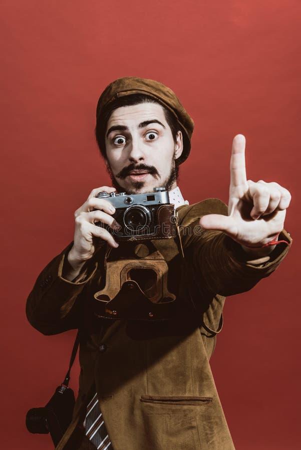 Sehr positiver Fotograf, der im Studio mit Filmkamera aufwirft lizenzfreie stockbilder