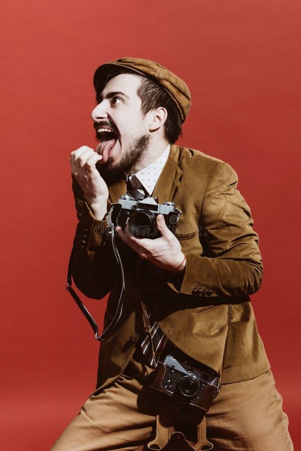 Sehr positiver Fotograf, der im Studio mit Filmkamera aufwirft stockfotos