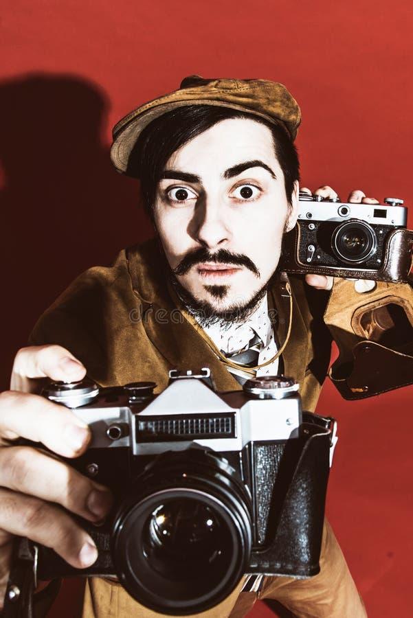 Sehr positiver Fotograf, der im Studio mit Kameras aufwirft stockbild