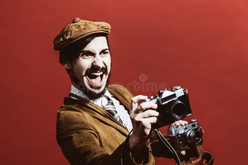 Sehr positiver Fotograf, der im Studio mit Kameras aufwirft lizenzfreie stockfotografie