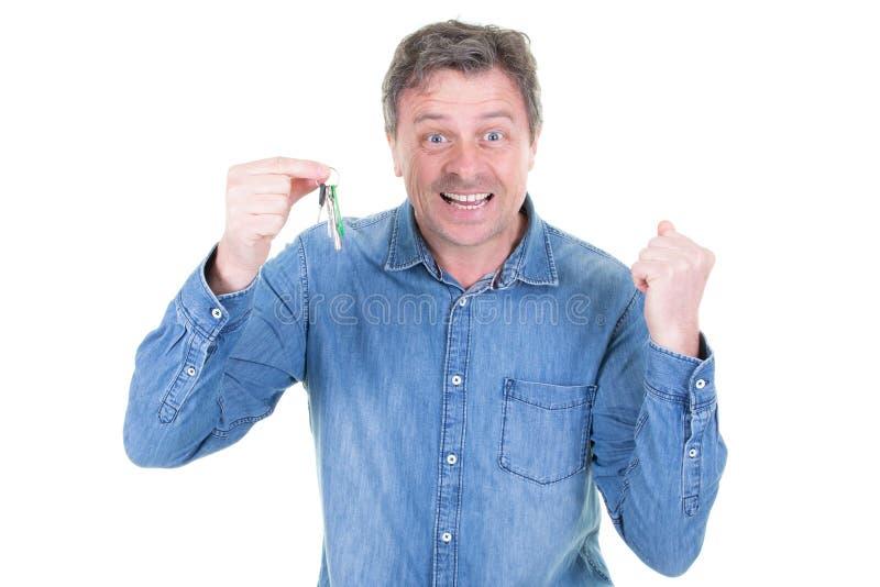 Sehr positiver glücklicher Mann, der Schlüssel in seinem neuen flachen Haus zeigend umzieht lizenzfreies stockfoto