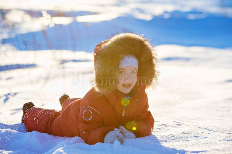 Sehr süßes schönes Kind des kleinen Mädchens in einem roten Overalllächeln stockbild