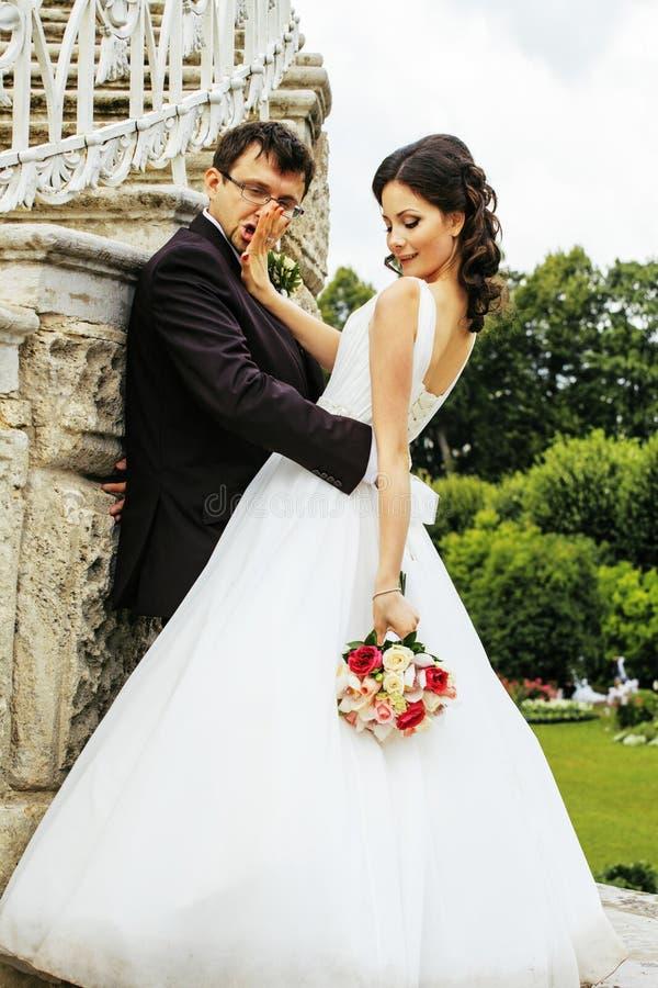Sehr schöne Braut mit dem Bräutigam, der in grüne Gleichheit umarmt und tanzt lizenzfreie stockbilder