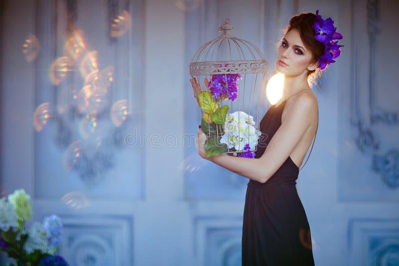 Sehr schöne Brunettefrau mit Blumen in ihrem Haar, das c hält stockbild